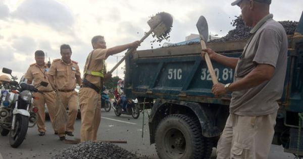 CSGT giúp lao công thu gom đá dăm